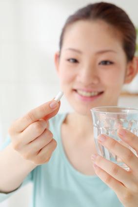 サプリメントを飲む女性